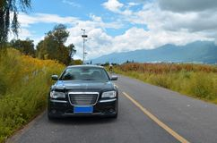 A black car parked on the roadside. ,this image can be used as a background Royalty Free Stock Images