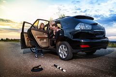 A black car, passengers in it and a scared girl on the road near baton and cap of Russian policeman. Staging an accident during a photo shoot royalty free stock photography