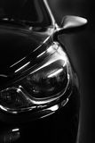 Black car in patches of light Stock Photos