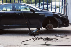 A black car with the removed front wheel. Black car on a Jack with the removed front wheel Royalty Free Stock Photo