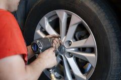 Auto mechanic changing car wheel Stock Photos