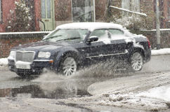 Black car rides on big puddle in snowy day. Sleet splash on a Ma Royalty Free Stock Image