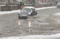 Black car rides on big puddle in snowy day. Sleet splash on a Manchester's road.03/03/2016 Manchester, England editoria. L Stock Image