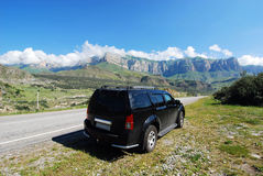 Black car on road to mountains Royalty Free Stock Photos