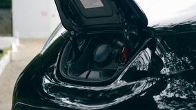 Black car`s hood with an electrical nozzle during recharge. 4K stock footage