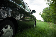 Black car on the side of the road in the green grass. Travel closeup Royalty Free Stock Images