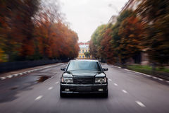 Black car speed drive on asphalt road in city at daytime Stock Photos