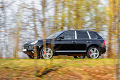 Black car speeding on road Stock Photography