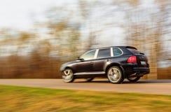 Black car speeding on road Royalty Free Stock Image