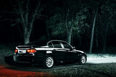 Black car stay in darkness forest at night. Black modern car stay in darkness forest at night Royalty Free Stock Photo