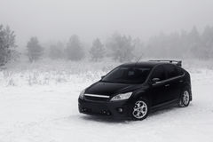 Black car stay in fog near pine forest at winter Stock Photo