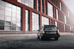 Black car Subaru Forester parked near modern red buildings in Moscow at daytime Royalty Free Stock Photos