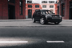 Black car Subaru Forester parked near modern red buildings in Moscow at daytime Stock Photos