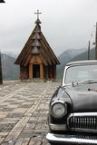Black car win. Black car victory in perfect good condition, the frame is not entirely visible, front view, mountains in the background and the church, temple Royalty Free Stock Photo