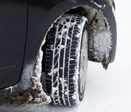 Black car with winter tyre in the snow Stock Photo