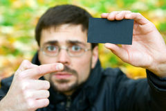 Black Card. Young man holding black business card and pointing it with his finger Stock Photos