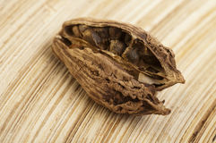 Black cardamom pods on wooden background Royalty Free Stock Images