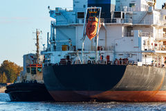 Black cargo ship. Entering the port of Riga, Europe stock images