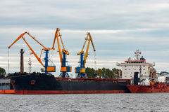 Black cargo ship. Loading in the port of Riga, Europe stock images