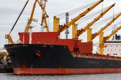 Black cargo ship. Loading in the port of Riga, Europe stock photos