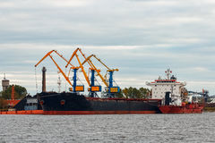 Black cargo ship. Loading in the port of Riga, Europe royalty free stock photography