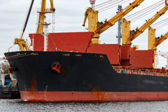 Black cargo ship loading. In the port of Riga, Europe stock images