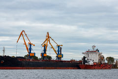 Black cargo ship loading. In the port of Riga, Europe Royalty Free Stock Photo