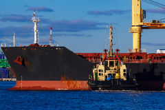 Black cargo ship mooring at the port. With tug ship support Stock Photos