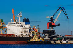 Black cargo ship mooring at the port. With tug ship support royalty free stock image