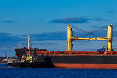 Black cargo ship mooring at the port. With tug ship support royalty free stock photo