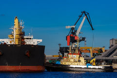 Black cargo ship. Mooring at the port with tug ship support Stock Photography