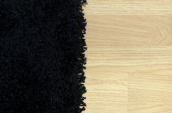 Black carpet and wooden surface. Royalty Free Stock Photography