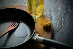 A black cast-iron frying pan for cooking food. Vegetable oil with spices. Stock Image