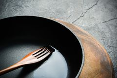 A black cast-iron frying pan for cooking food. Vegetable oil with spices. Royalty Free Stock Images