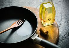A black cast-iron frying pan for cooking food. Vegetable oil with spices. Stock Photography