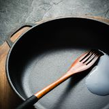 A black cast-iron frying pan for cooking food. Vegetable oil with spices. Royalty Free Stock Photo
