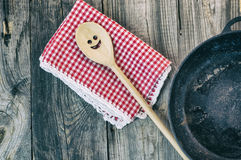 Black cast-iron frying pan with a wooden spatula for stirring Stock Images