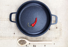 Black cast-iron frying pan, wooden spoon, red hot peppers and sp Stock Photo