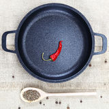 Black cast-iron frying pan, wooden spoon, red hot peppers and sp Stock Images