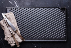 Black cast iron grill surface and fork and knife set Royalty Free Stock Images