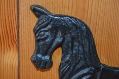 Black cast iron horse head. Door stop. Pine door. Black cast iron horses head.detail from a door stop in front of a pine door background. Signs of age with some Royalty Free Stock Photos