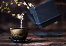 Black cast iron kettle and a cup Royalty Free Stock Image