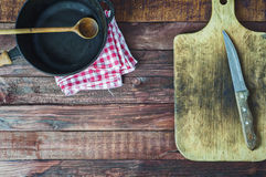 Black cast iron pan and cutting board on brown wooden surface Stock Photography