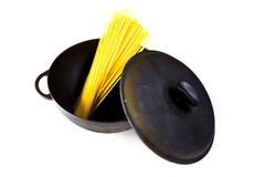Black cast iron pot with raw pasta, isolated on a white. Background royalty free stock photography