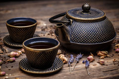 Black cast iron teapot. And cup of tea on wooden background Stock Images