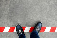Black casual shoes standing on red and white line. Crossing the limit. Disobey and act against the rule Stock Photography