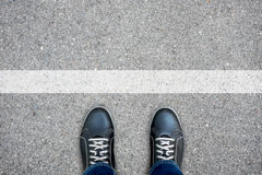 Black casual shoes standing at the white line Royalty Free Stock Photos