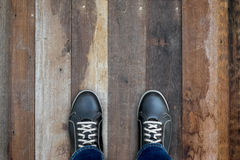 Black casual shoes standing on wooden floor Royalty Free Stock Images