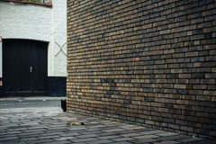 Black cat behind the brick wall on the street in Bruges, Belgium Stock Image