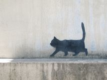 The cute cat sit. A black cat drawing on the wall stock photography